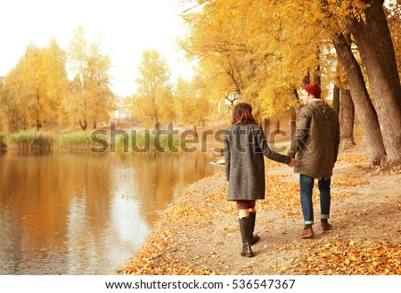 Beautiful young couple walking near lake in autumn park