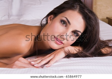 Beautiful young Czech woman lying topless in bed