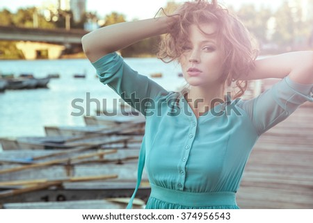 Beautiful young fashion model in green turquoise dress and fashion makeup and hairstyle is posing on pier, posing and looking at camera. close up. sunset effect on camera. with passion.