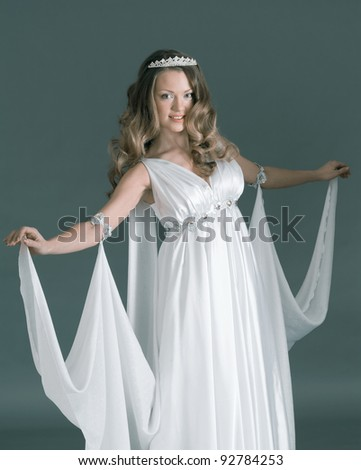 Beautiful young female wearing white dress in antique style  .Like goddess