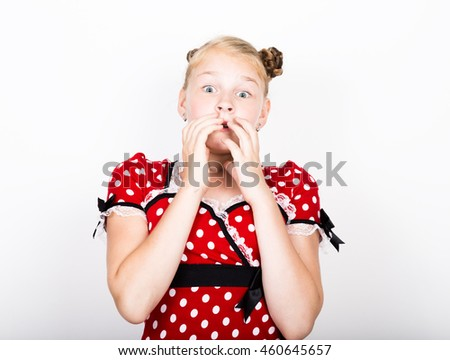beautiful young girl dressed in a red dress with white polka dots. Funny kids pamper and posing