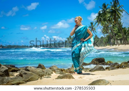 Beautiful young girl dressed in a sari posing on the beach