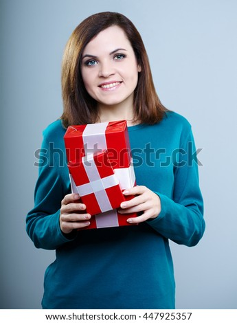 beautiful young girl in a blue t-shirt holding gift boxes on gray background