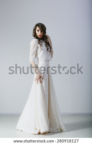 beautiful young girl in a white wedding dress studio