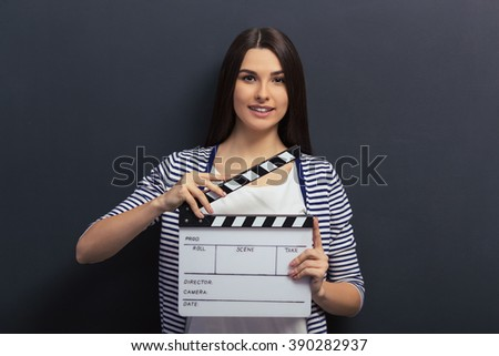 Beautiful young girl in casual clothes is holding a clapperboard, looking at camera and smiling, standing against blackboard