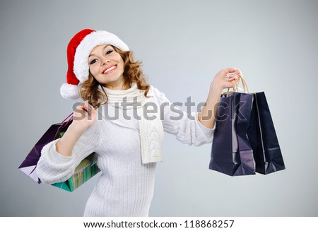 Beautiful young girl in red Santa hat with shopping bags