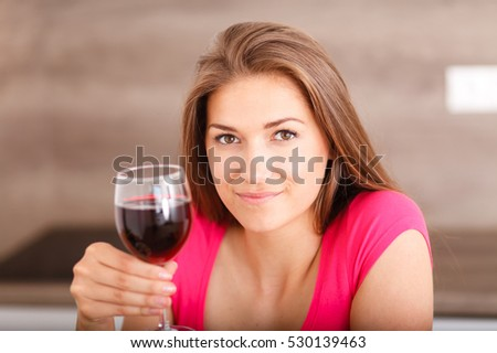 Beautiful young girl posing in the kitchen with a glass of red wine. (Shallow DOF).