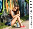 Beautiful young girl sitting near a wall with graffiti. Outdoors - stock photo