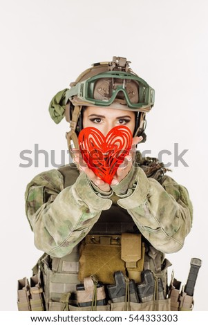 beautiful young girl soldier holding red heart in his hands