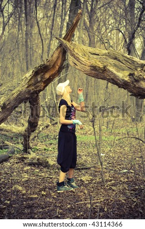 Young girl standing under a fallen tree in the forest stock photo