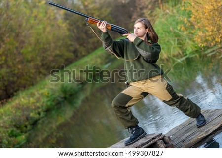 beautiful young girl the hunter with a gun in uniform, aiming at flying ducks standing in water