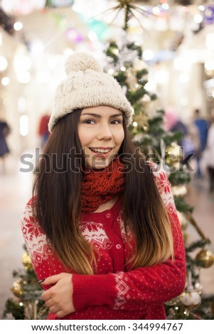Beautiful young girl went shopping for Christmas presents to a decorated mall with many bright lights,fur trees.Attractive young shopper girl go shopping at the mall,buy holidays presents for New Year