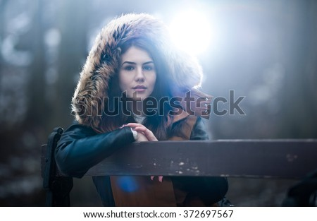 Beautiful young girl with brown fur cape enjoying the winter scenery sitting on the bench in park. Teenage girl posing, winter concept. Young female with snowflakes around in bright cold day