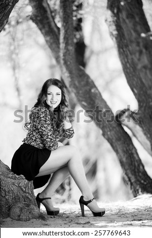 Beautiful young girl with long hair on nature near a tree in a short skirt, black and white