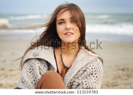 Beautiful young happy woman portrait against seascape, long hair fluttering in the wind, looking at camera, casual autumn fashion, healthy lifestyle