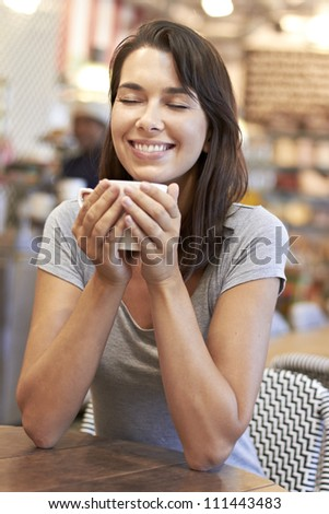 Beautiful young lady smiling while enjoying her warm coffee in a coffee shop