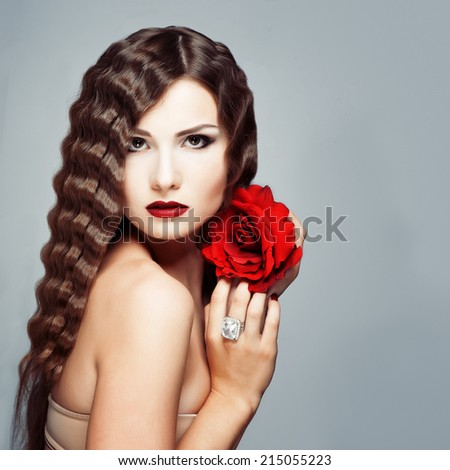Beautiful young model with red lips and red rose