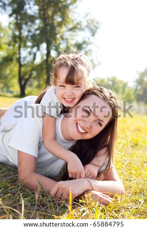 beautiful young mother and her daughter in the park on a sunny autumn day