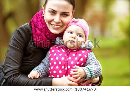 beautiful young mother daughter relaxing sitting grass background spring meadow green grass trees