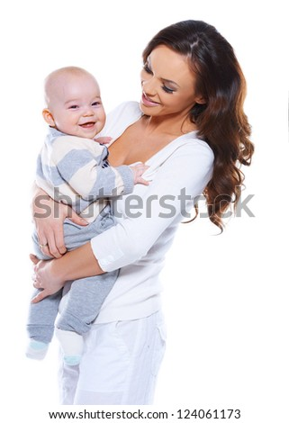 Beautiful young mother with a happy baby who is beaming at the camera clasped in her arms isolated on white
