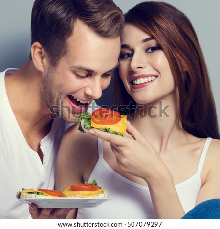 Beautiful young playful couple eating crispbread with cheese and tomato together. Caucasian models in vegetarian, weight lossing, dieting, healthy food concept studio shot, against grey background.