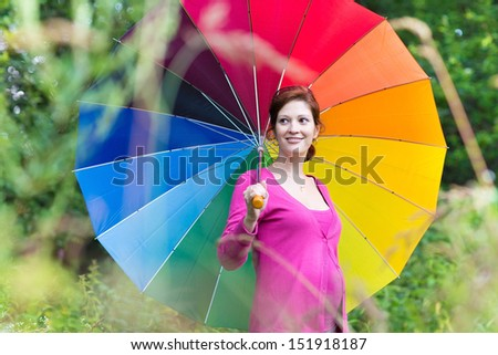 Beautiful young pregnant woman walking under a colorful umbrella on a warm autumn day