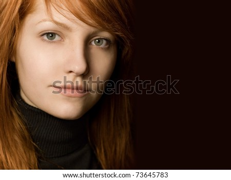 Beautiful young redhead girl with attitude, strong portrait on black background.