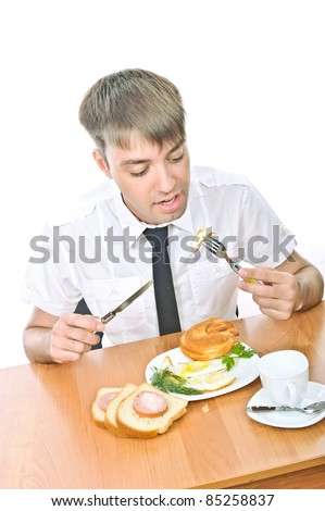 beautiful young Russian guy sitting at the table and eat breakfast, isolated over white