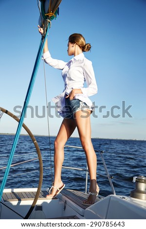 stock photo beautiful young sexy brunette girl in a dress and makeup summer trip on a yacht with white sails 290785643