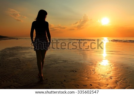 beautiful young slim girl standing on sandy beach at sea at the sunset
