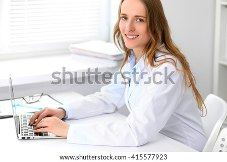 Beautiful young smiling female doctor sitting at the table near window in hospital