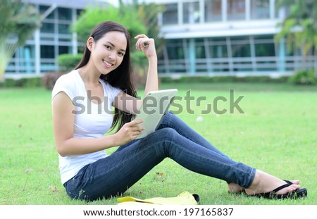 Beautiful young student relaxing on green grass with computer tablet