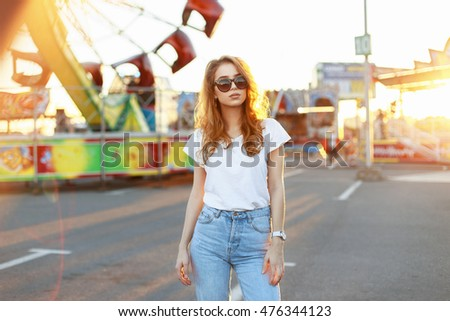 Beautiful young stylish woman in sunglasses walking in the amusement park at sunset.