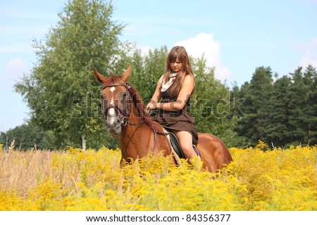 Beautiful young teenager girl in brown dress and chestnut horse at the field with yellow flowers