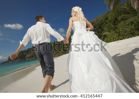 Beautiful young wedding couple, bride and groom enjoying sunset, walking barefoot on beach and playing with each other. Lifestyle wedding on tropical island in caribbean or Hawaii.