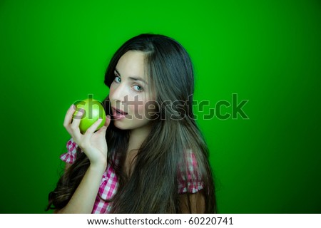 Beautiful young woman about to bite a green apple. Green background.