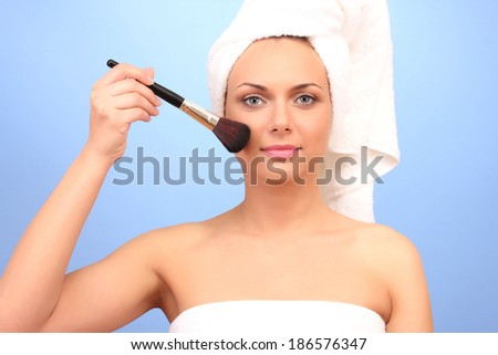Beautiful young woman after shower with a towel on her head and a brush make-up in hand on a blue background close-up