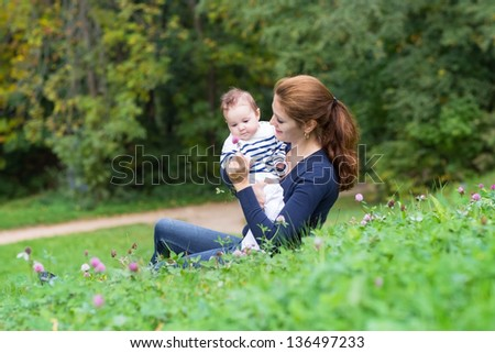 Beautiful young woman and her little bay relaxing in the garden