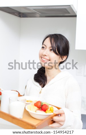 beautiful young woman carrying tray with food and drink