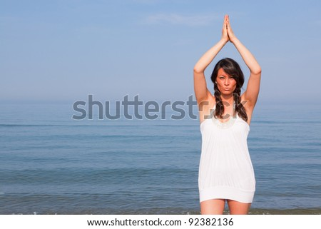 Beautiful Young Woman Doing Yoga Exercises at Seaside