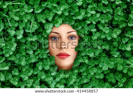Beautiful young woman face surrounded by clover grass flowers