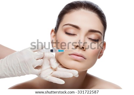 Beautiful young woman gets beauty injection in lips from sergeant. Isolated over white background.