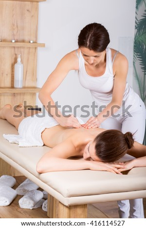 Beautiful young woman getting a back massage/ Image of young beautiful woman who laying on her stomach. She is receiving a back massage.