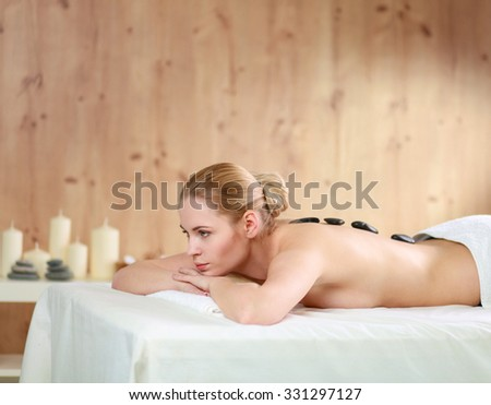 Beautiful young woman getting spa massage, lying on salon