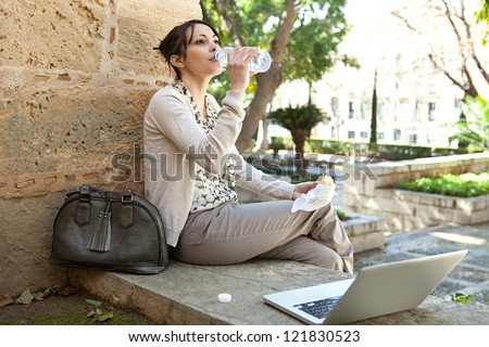 Beautiful young woman having her lunch break in a city park, using a laptop computer and drinking water from a bottle.