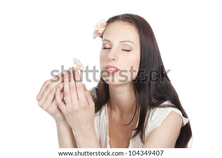 Beautiful young woman holding a flower at face, isolated on white
