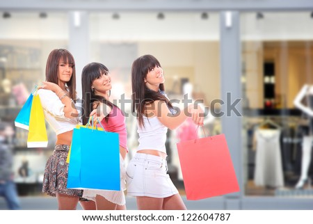 Beautiful young woman holding shopping bags in front of the shop