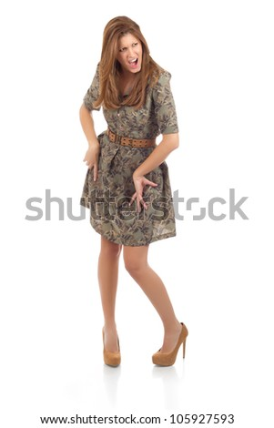 Beautiful young woman in a floral pattern green dress posing in high heels on white background, with a confident chic facial expression