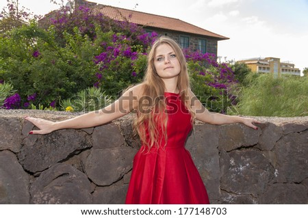 Beautiful Young Woman In A Red Dress. Tenerife. Park Taoro.