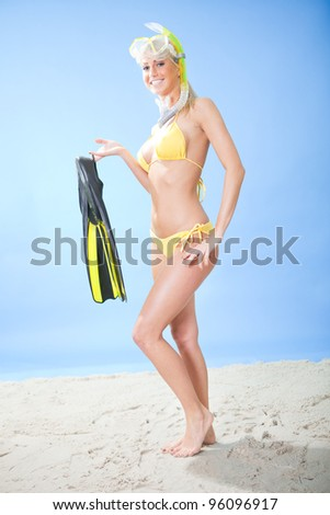 Beautiful young woman in bikini with snorkel equipment at the beach